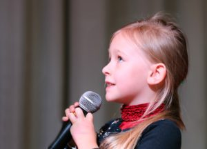 Young girl speaking into microphone